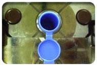 Blue vial in machine mold with cap off